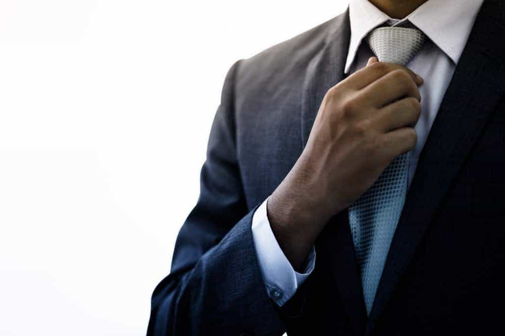 A man in a formal suit with a necktie.