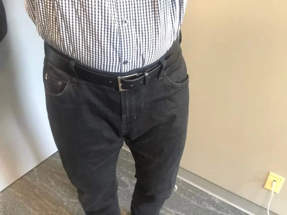 Black AG jeans for men with shirt tucked.