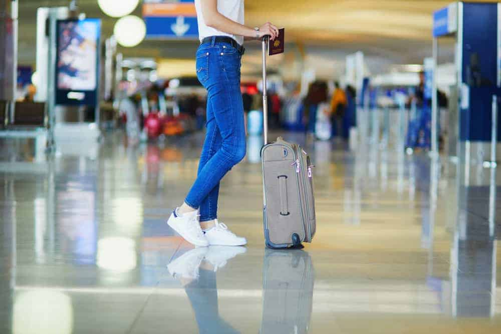 Airport fashion of a person in white shirt, jeans, and sneakers.