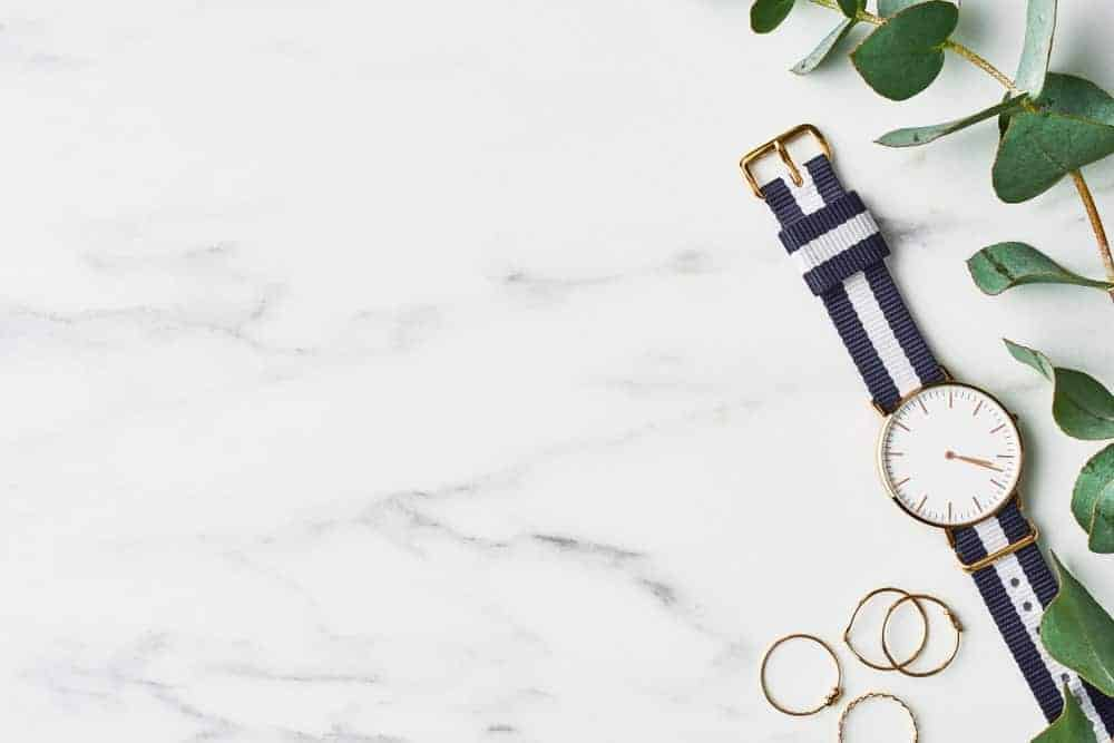 Women's watch with NATO watch band beside leaves on a marble background.