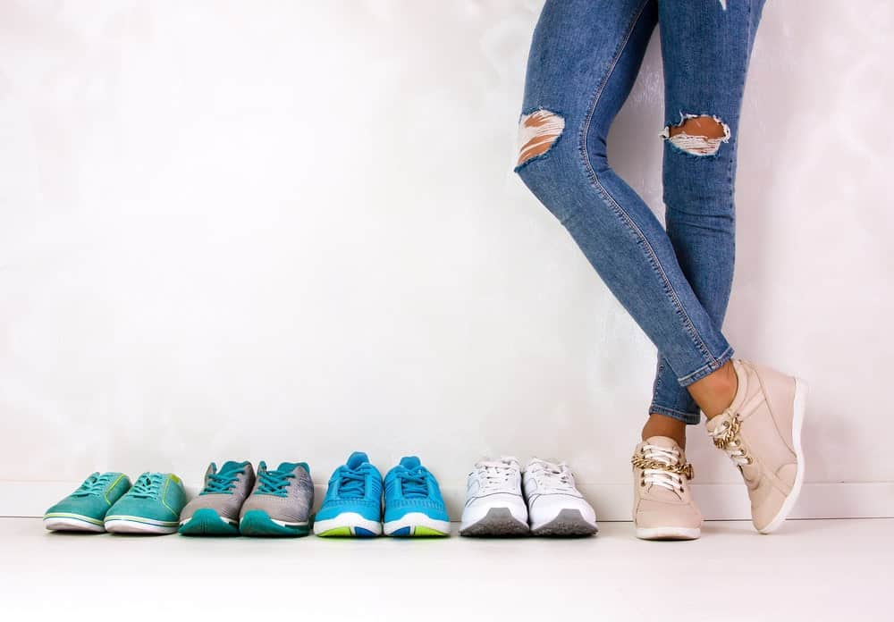 Shot of a woman's legs in ripped jeans and wearing a pair of beige sneakers beside a row of multi-colored sneakers.