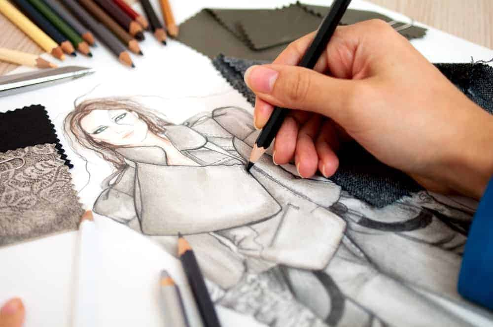 A designer drawing a female model's apparel.