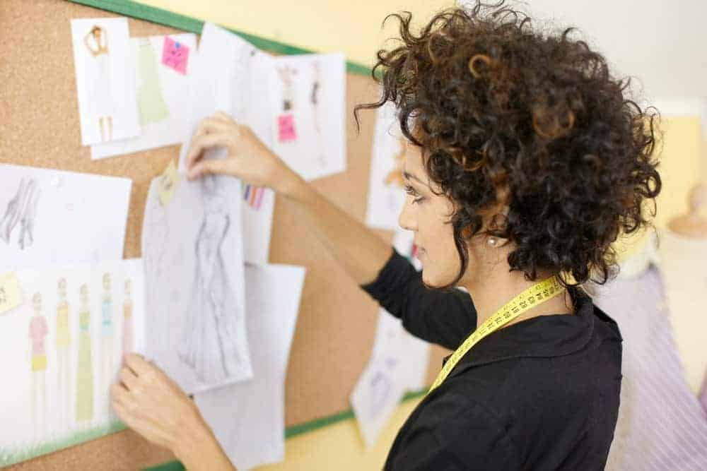 Woman with a curly hair putting a paper on a board.