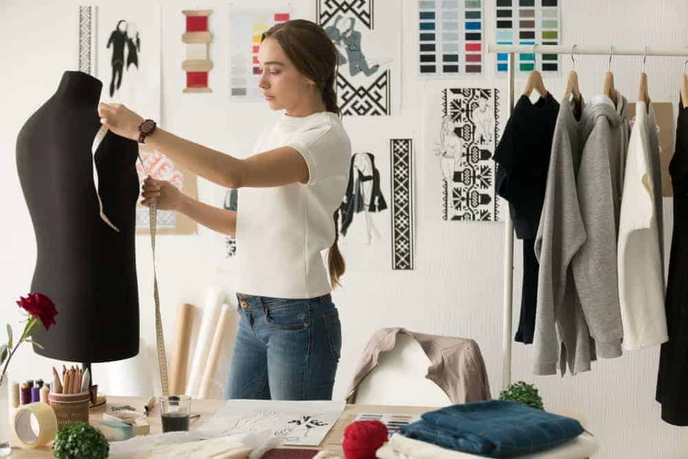 Woman in a white t-shirt measuring a fit model.