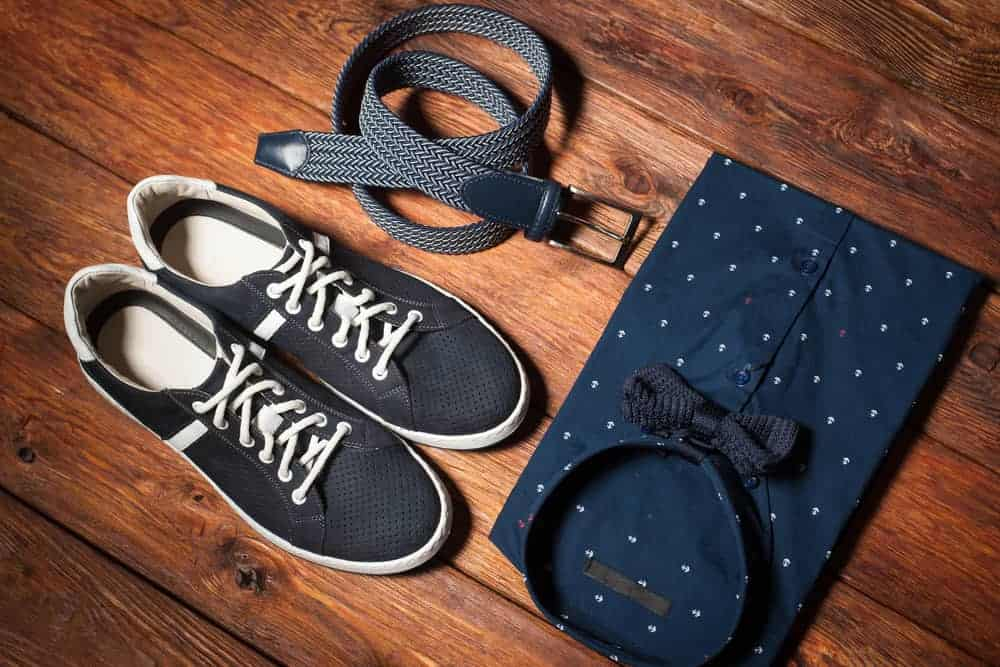 A pair of sneakers, a belt, and a shirt with a tie on a wooden background.
