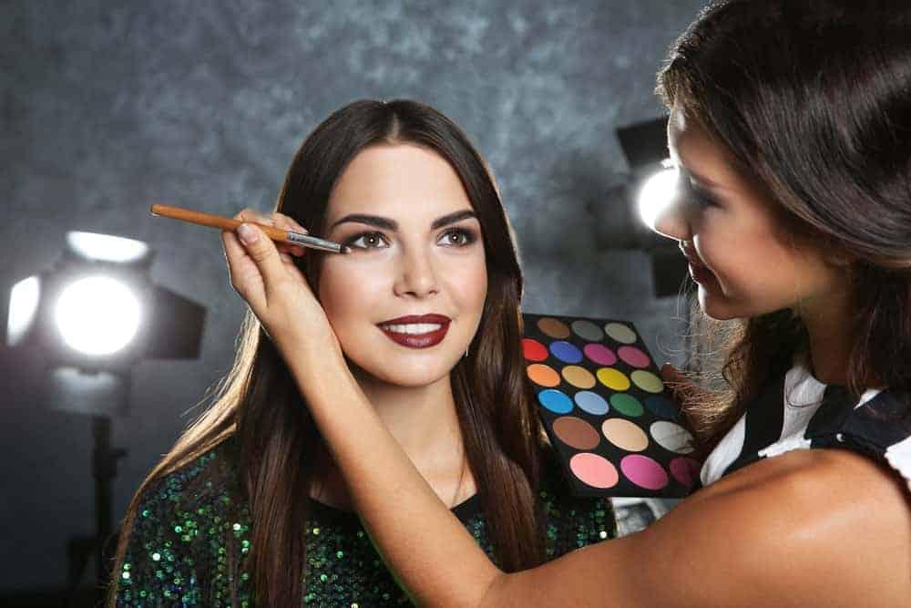 Beautiful brunette getting a makeup from a female makeup artist.