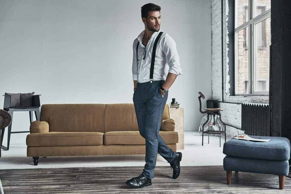 Male model in stylish clothing striking a pose in a chic living room.