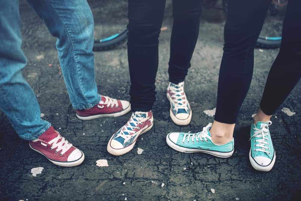 A trio wearing canvas sneakers.