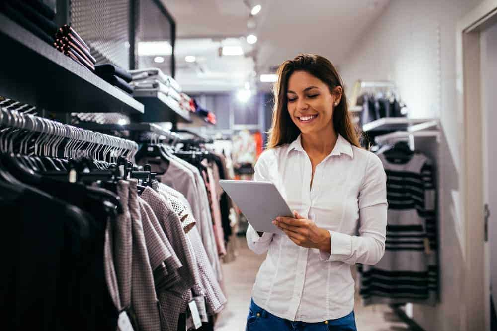 Woman on a white shirt holding a notepad while scanning the store.