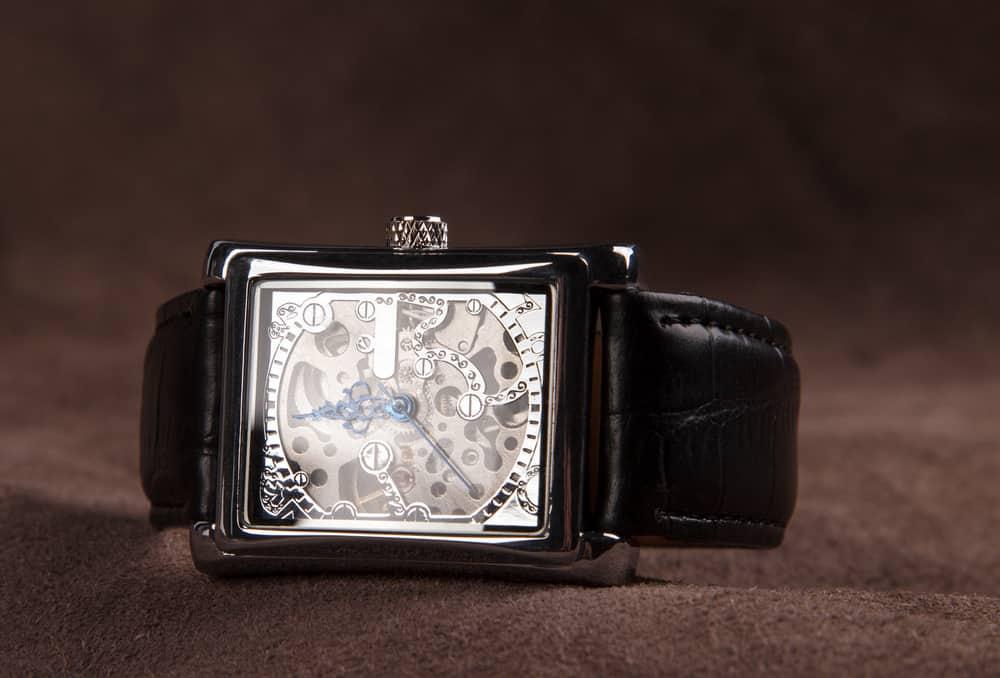 A close look at a rectangular analog watch for men.