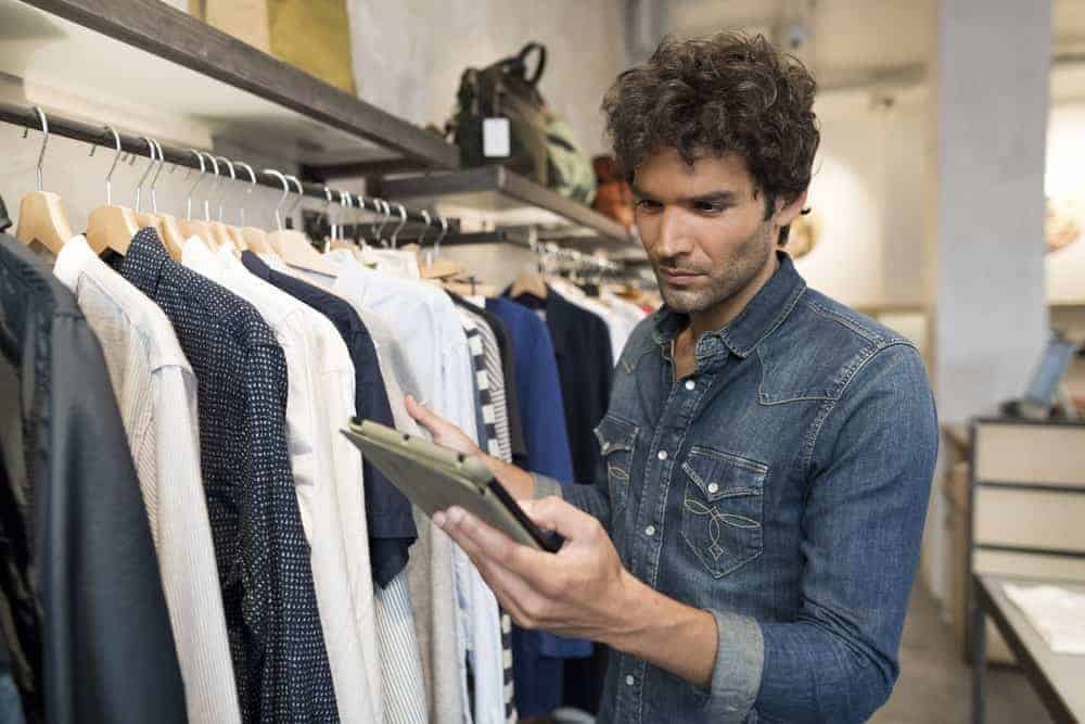 Man on a denim shirt holding a notepad while checking the merchandise in the store.
