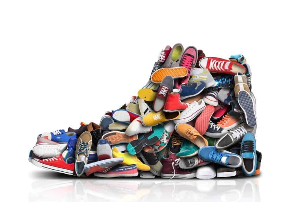 A pile of sneakers make a collage of a sneaker.