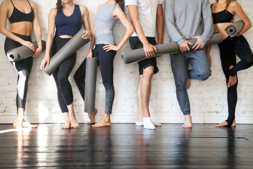 Group of sporty people holding mats as they stand against the brick wall.