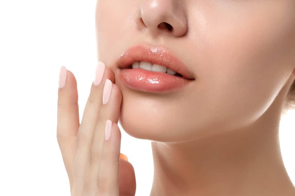 A close up look at a woman wearing chapstick.