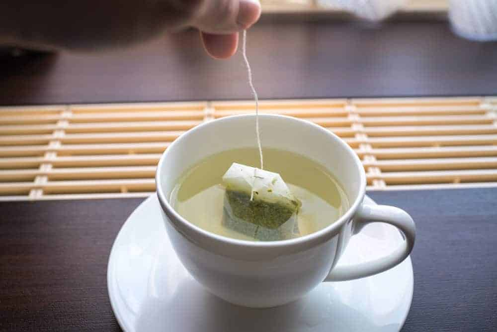 Soaking green tea bag on a teacup with hot water.