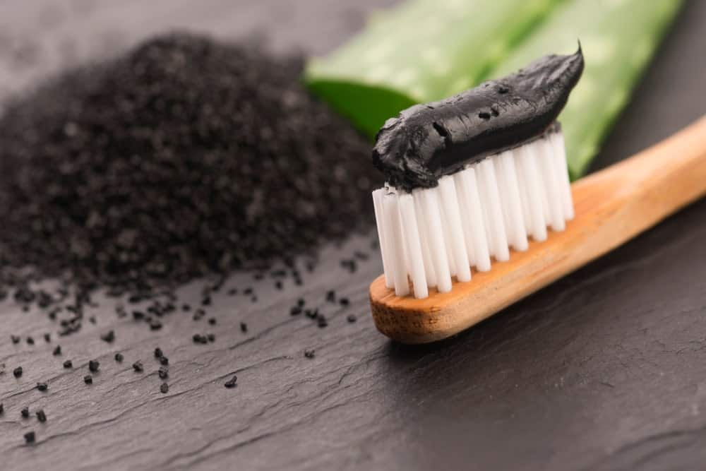Charcoal and aloe vera toothpaste spread on a bamboo toothbrush beside grounded charcoal and slices of aloe vera.