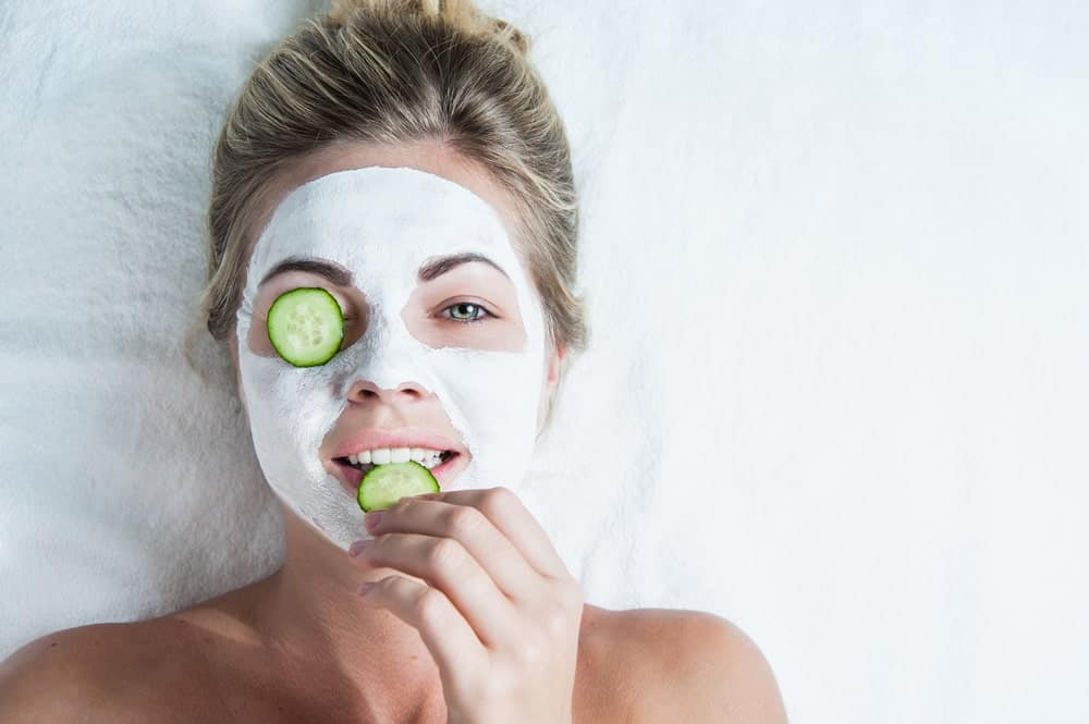 Woman lying down on white sheet with her face covered in a face mask and slices of cucumber on her eye and lip.