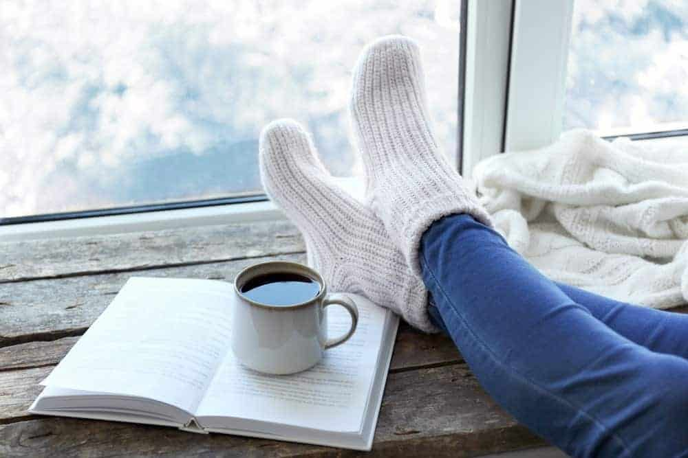 A cup of coffee on an open book beside a pair of raised feet covered in jeans and socks on wooden desk by the window.