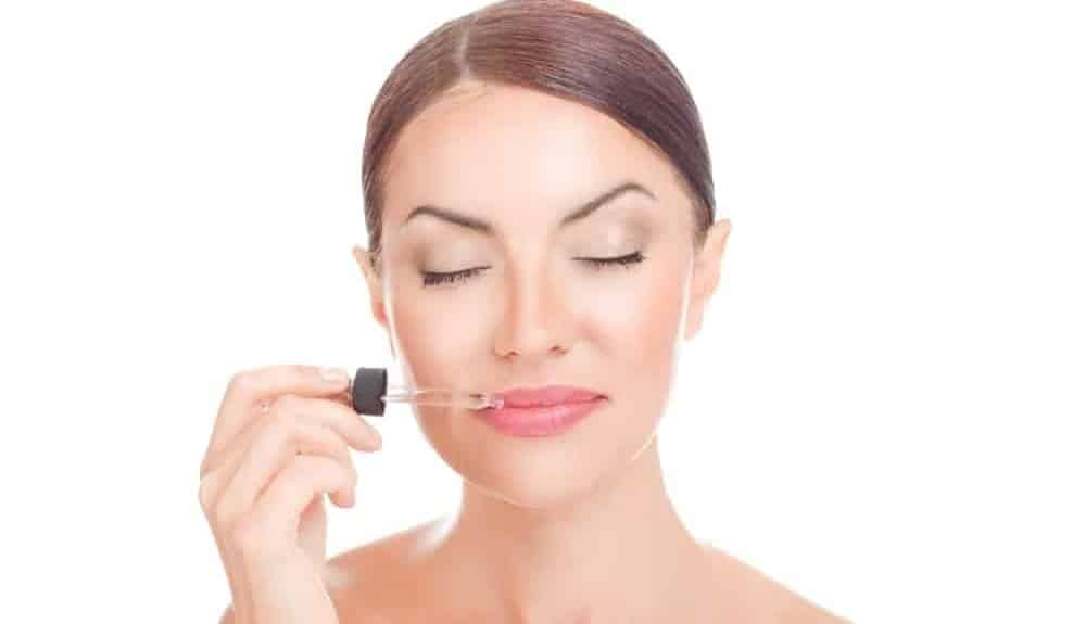 Woman applying essential oil on her lips.