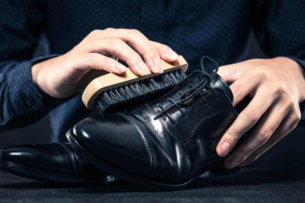 A close look at a man polishing his black leather shoes.