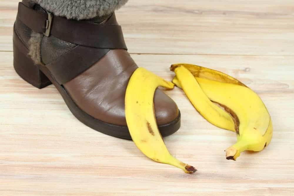 Peeled banana skin lies on top of a brown leather shoe and on wooden flooring.
