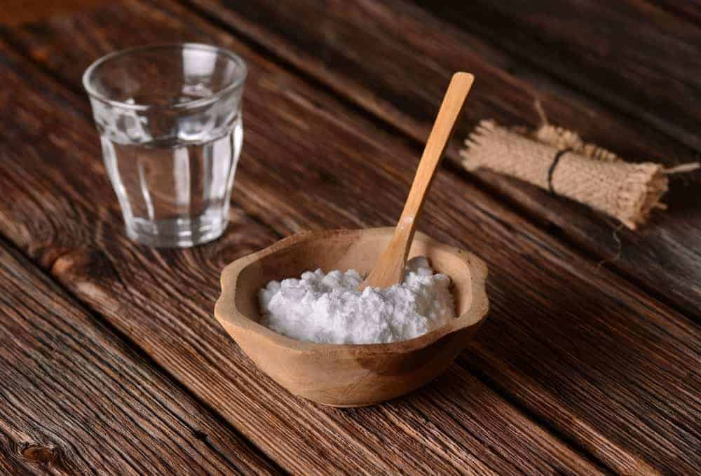 A bowl of baking soda with wooden spoon and a glass of water beside it.