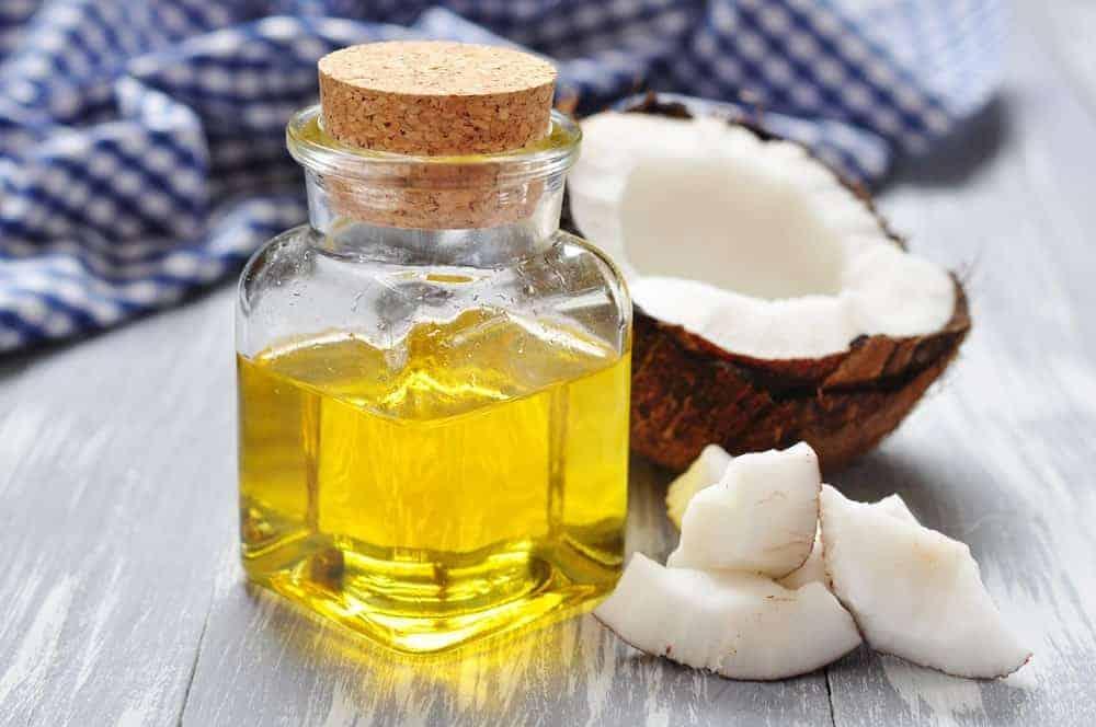 A small bottle of coconut oil beside an open coconut.