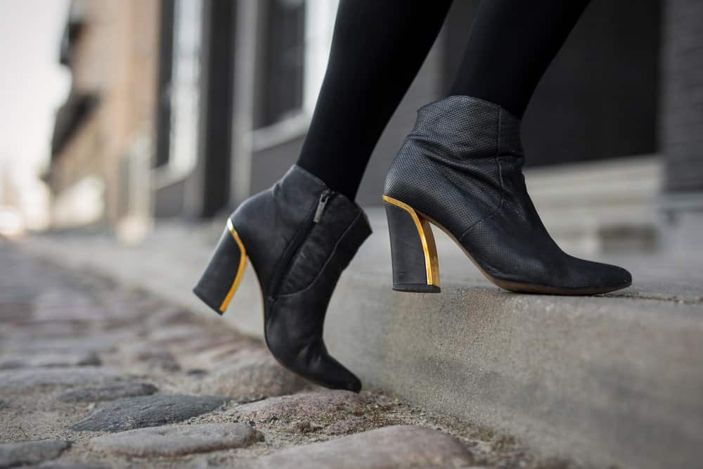 Woman in ankle boots climbing a stoop.