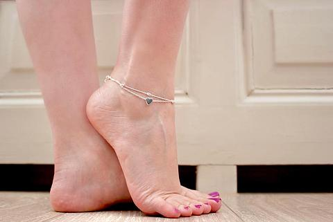 Woman bare feet with heart ankle bracelet.