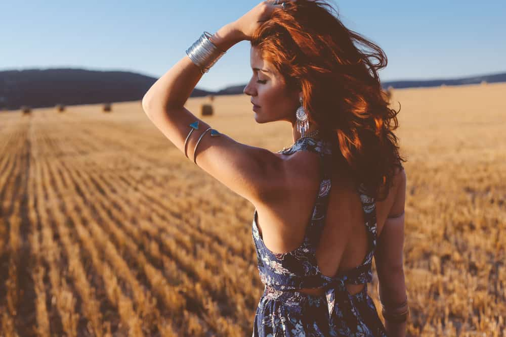 Model with armlets posing in autumn field.