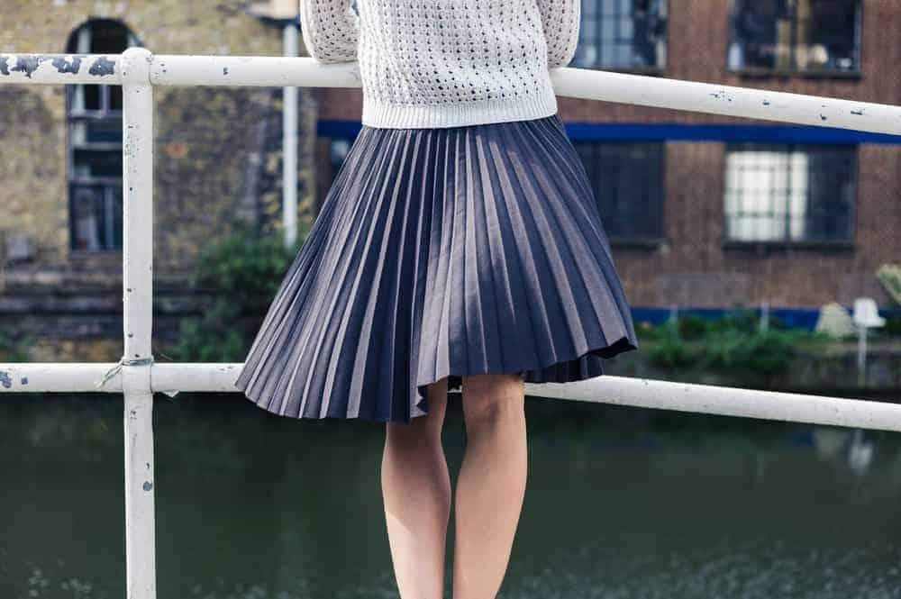 Woman on a bridge wearing an asymmetrical skirt.