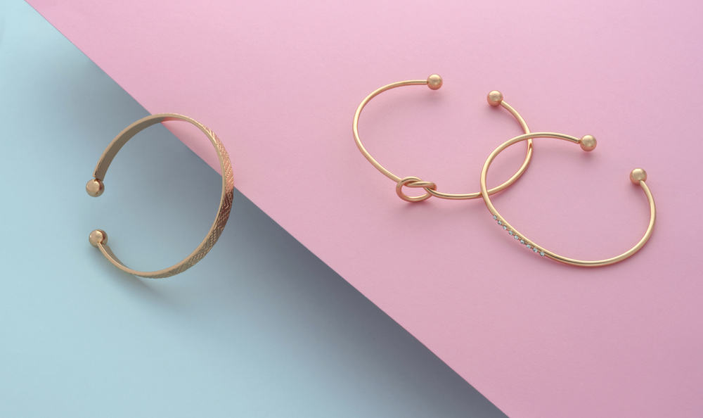 Three gold bangles against blue and pink background.
