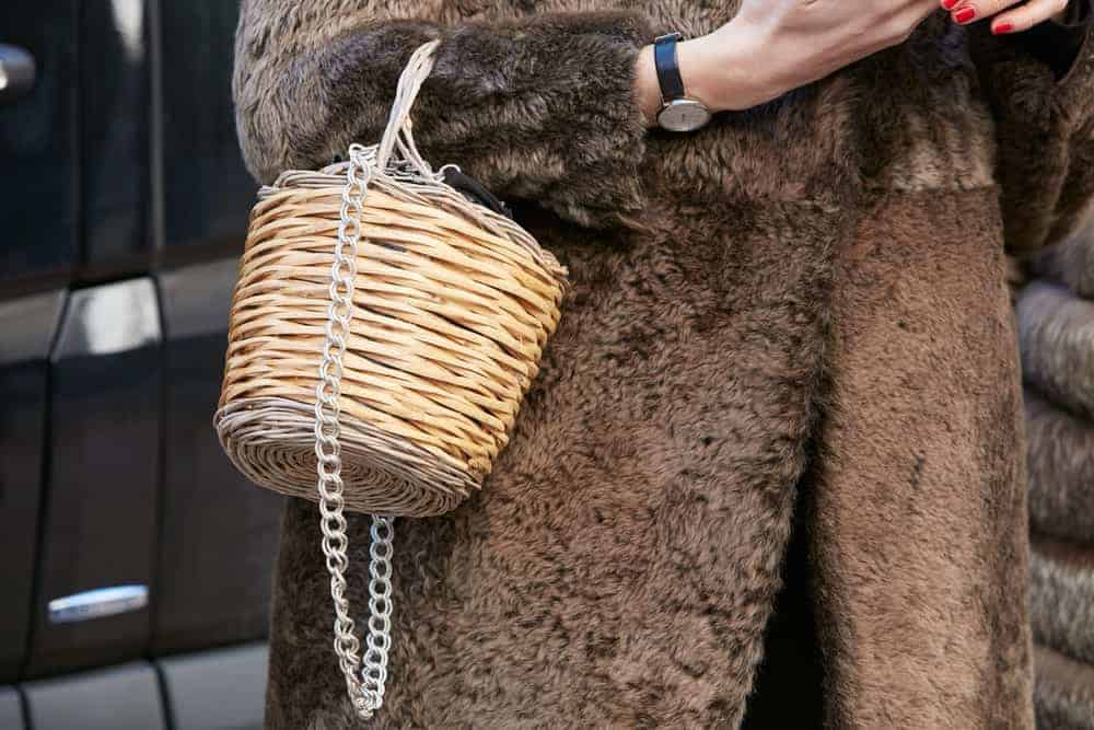 Woman in a brown fur coat with wicker basket bag.