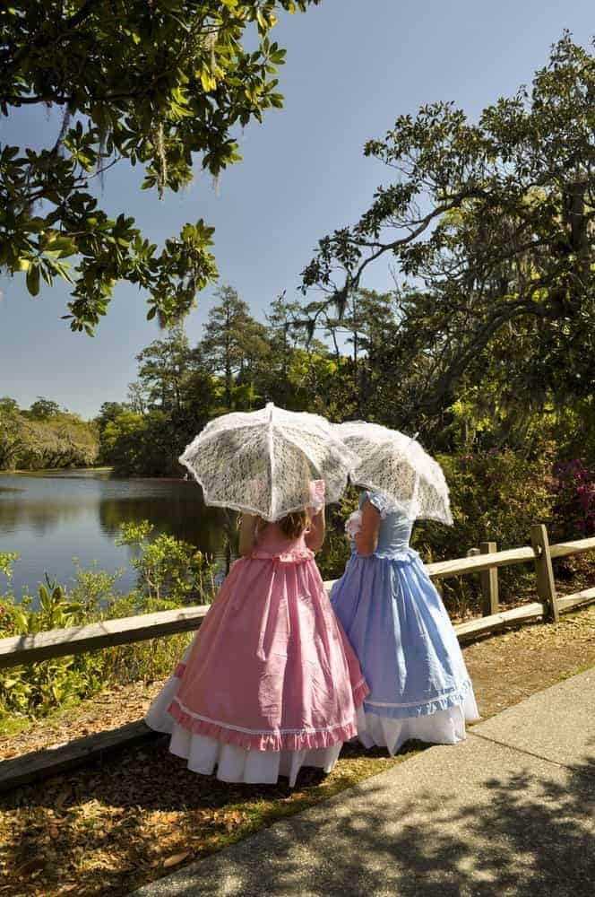 Two Southern belles with umbrellas enjoying the lake view.