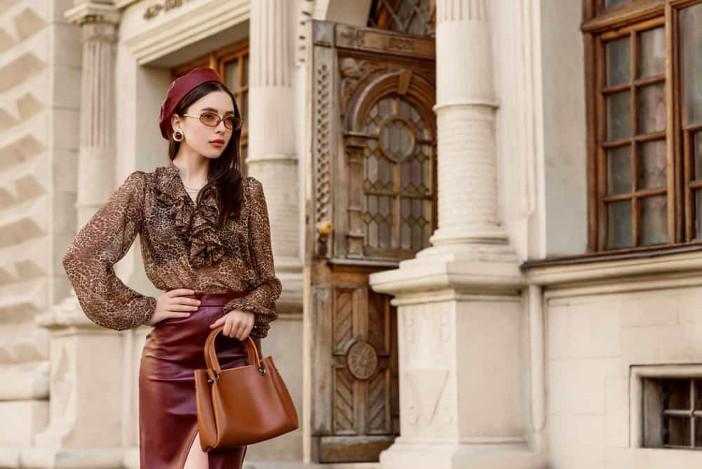 Woman wearing leather beret, skirt, leopard print blouse, beige sunglasses, and a leather handbag.