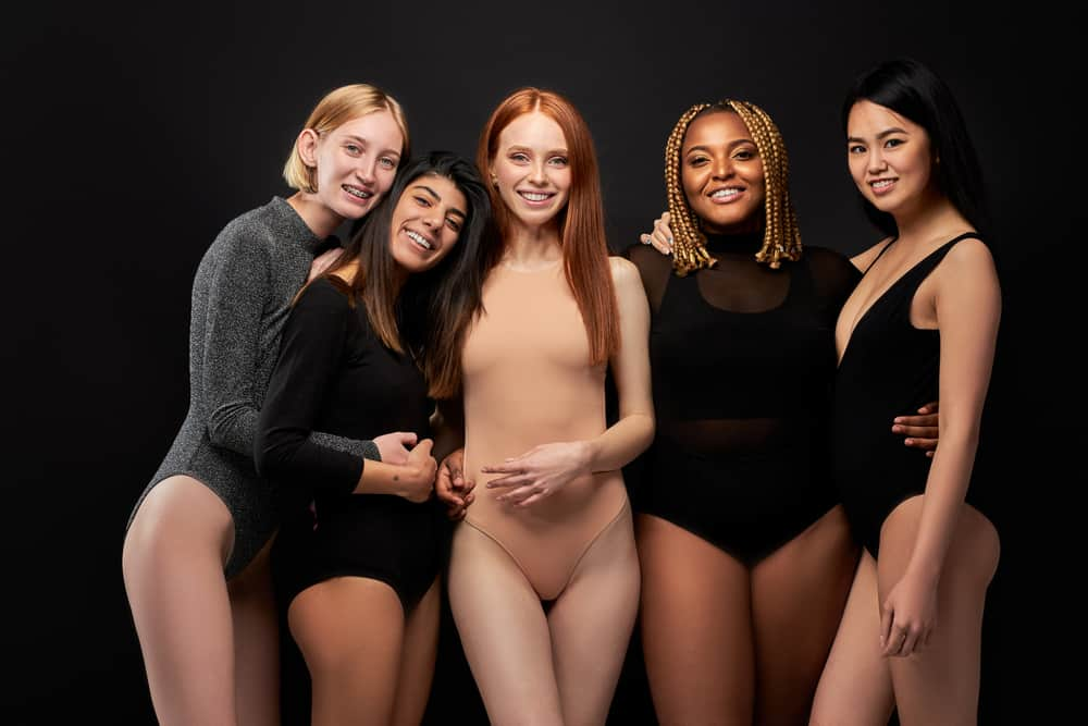 Women wearing bodysuits against the black background.