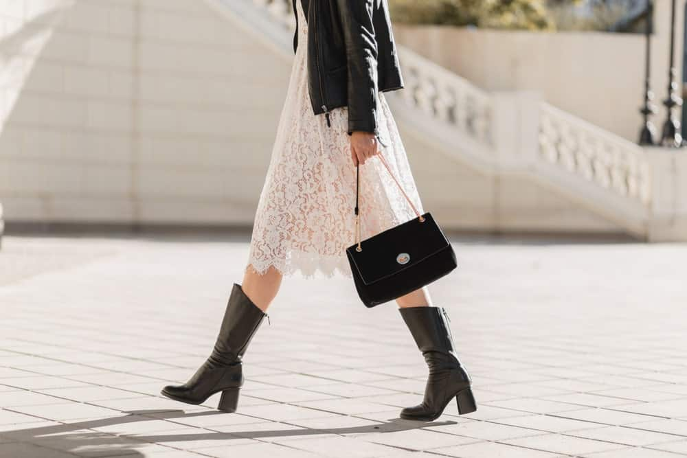 A woman in white lace dress and high leather boots walking on a street.
