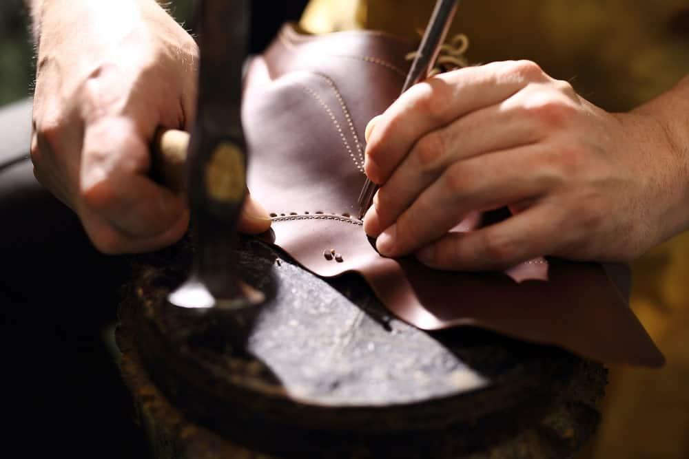 Shoemaker stitching a boot.