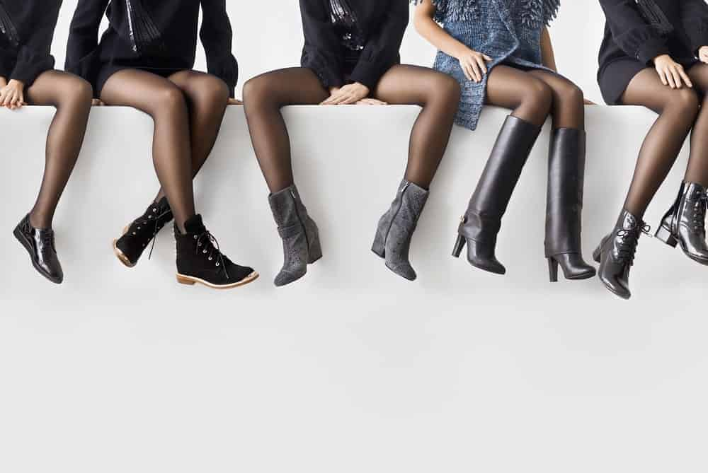 Women sitting on a wall wearing black boots.