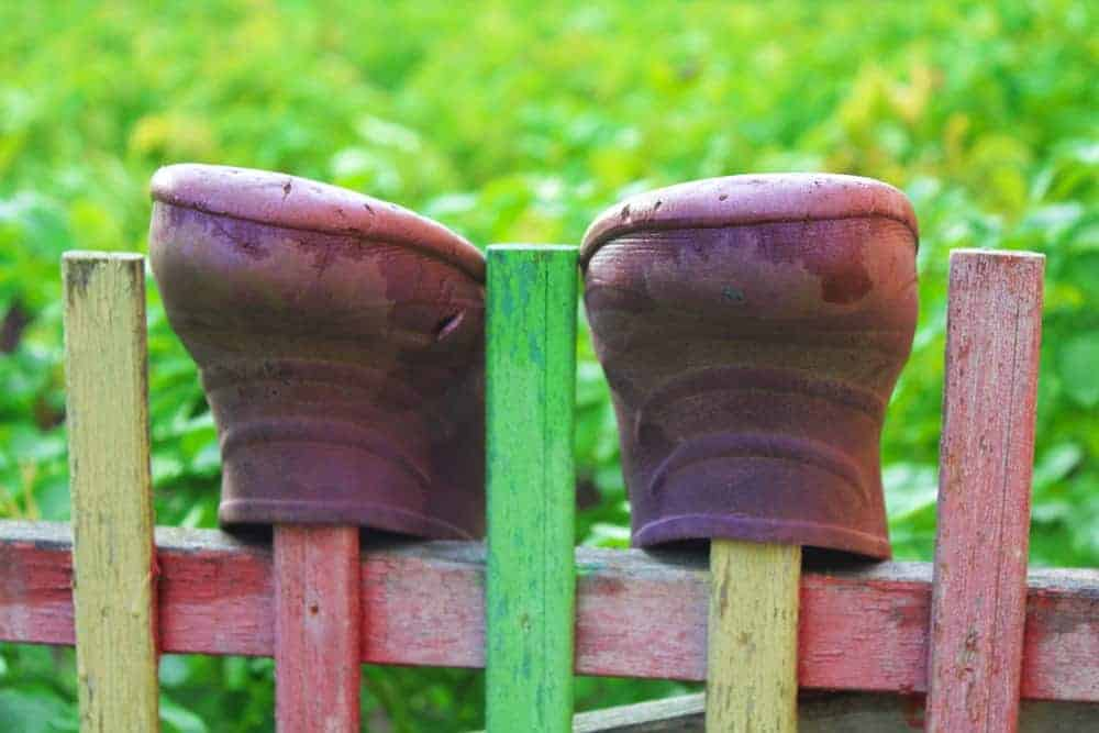 Boots on a wooden fence.