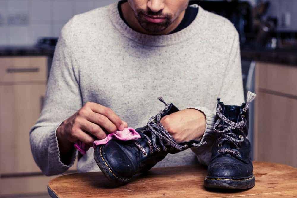 Man is polishing his boots.