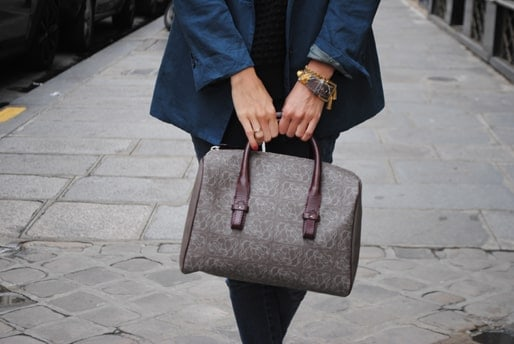 Woman holding a Boston taupe bag.