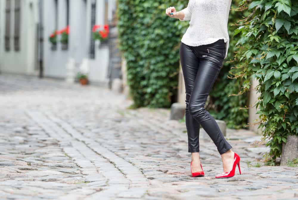 Woman wearing black leather pants and red high heel shoes in old town.