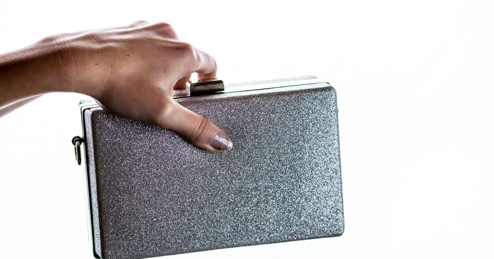 Woman hand holding a glittery silver clutch bag.