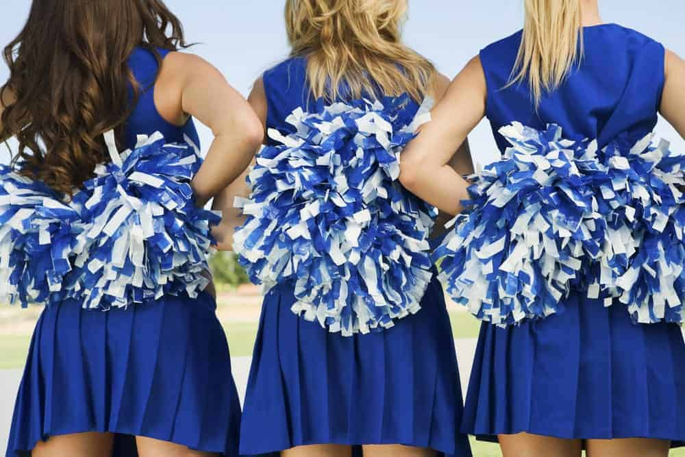 Back view of three cheerleaders holding pom poms.