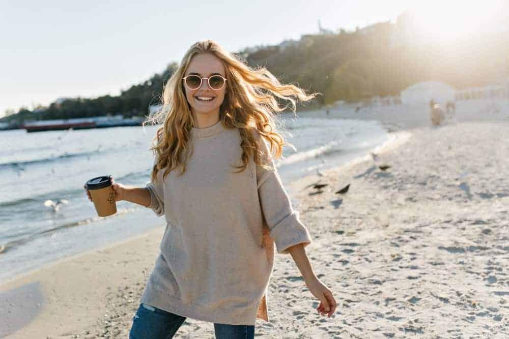 Woman in a boyfriend sweater posing near the ocean.