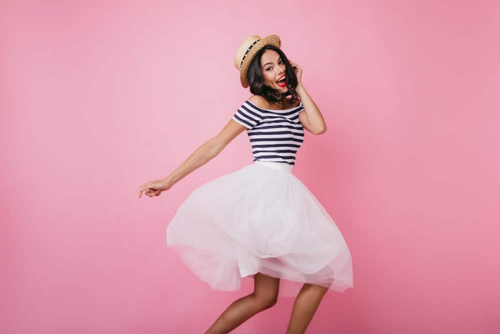Cheerful woman wearing a straw hat, striped shirt, and white bubble skirt.