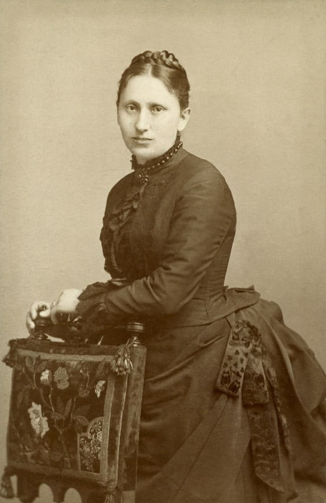 Victorian woman posing behind a chair.
