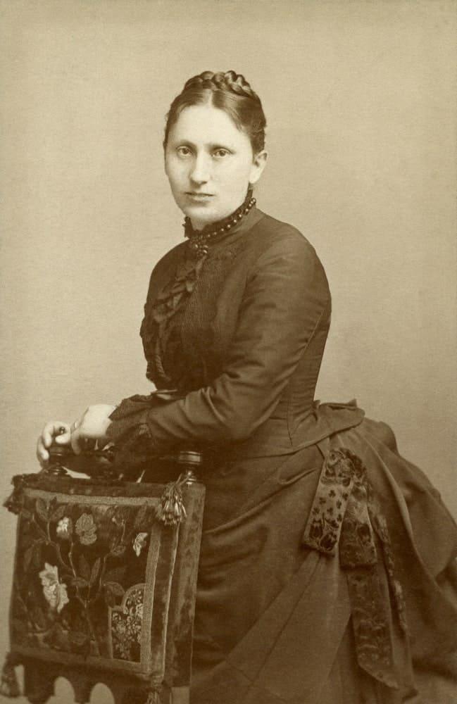 Victorian woman posing behind a chair.
