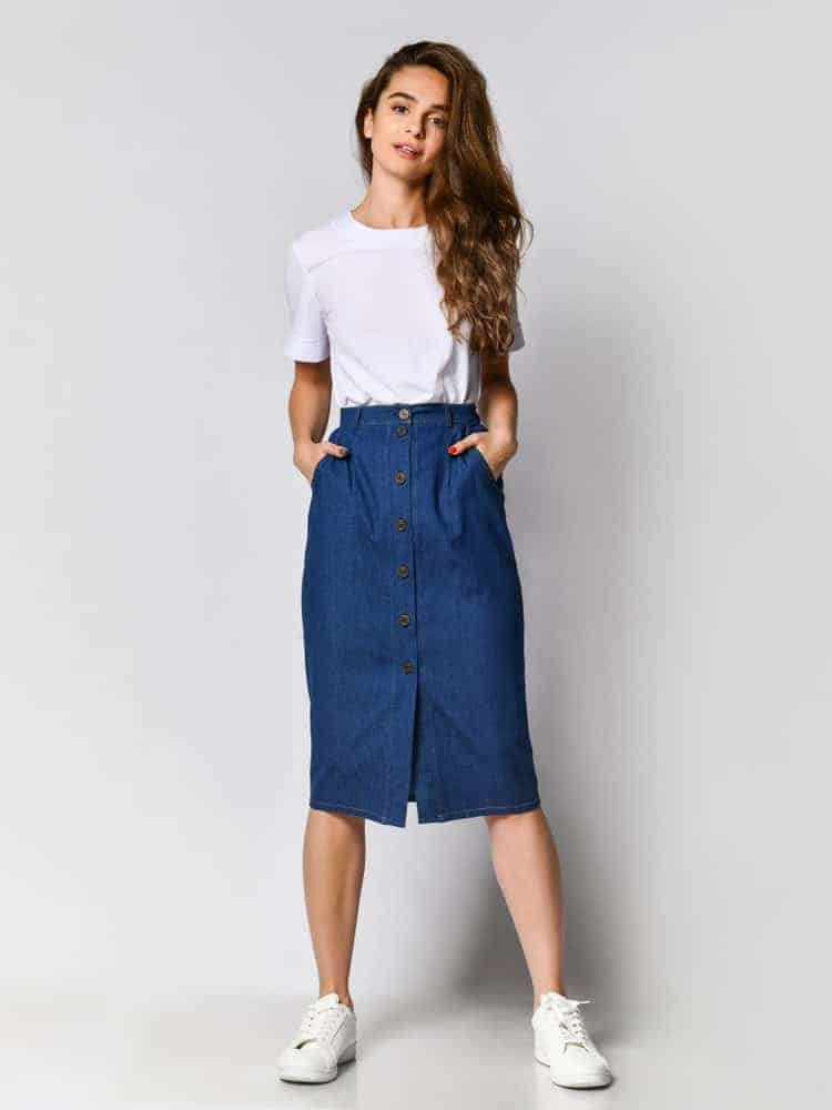 Lady with her hands on the side pockets of her button up skirt.